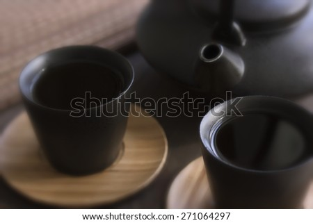 Black teapot and two teacups with tea on bamboo plates. Shallow DOF, Blur, Toning - stock photo