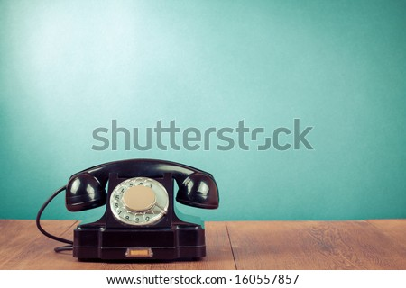 Black telephone on table in front mint green background - stock photo