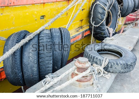 Black tire is hanging around the side of yellow boat for cushioning - stock photo