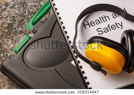 Black toolbox with earphones and health and safety document - stock photo