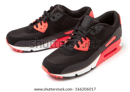 Black trainers with pink details isolated on white background. - stock photo