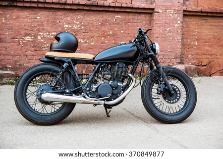 Black vintage custom motorcycle motorbike caferacer with black full face helmet in front of brick wall. Ready for a wild ride. - stock photo