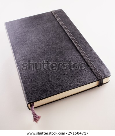 Black vintage notebook over white background, vertical image - stock photo