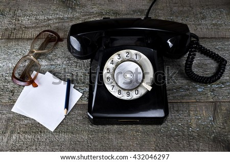Black vintage phone on wooden background with sheet for notes, pencil and old glasses close-up, top view, pick up the phone - stock photo