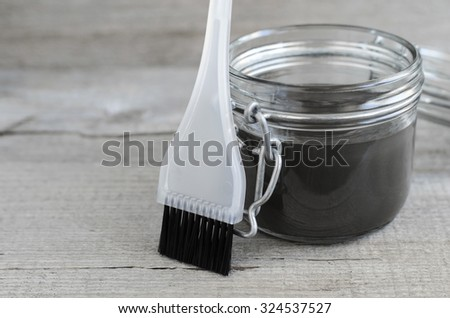 Black volcanic cosmetic clay in a glass jar - stock photo