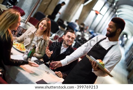 Black waiter serving terrace restaurant guests at table.Focus on the man - stock photo
