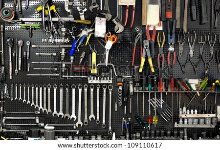 Black wall with many tools in workshop - stock photo