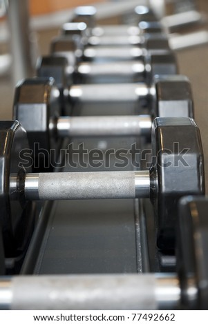 Black weights on a rack in a gym - stock photo