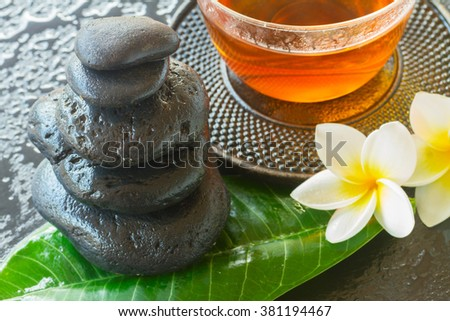 black wet zen stones with frangipani flowers and green fresh leaf - stock photo