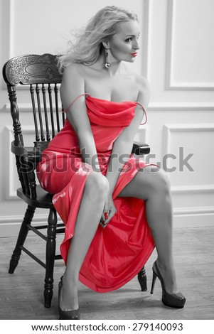 Black white and red color photo of the sexy sensual blonde woman in red dress with long hair sitting on the chear - stock photo