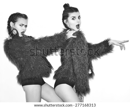 Black white fashion lifestyle portrait of two pretty best friends girls,wearing bright swag style pink fur,jewelry,having fun and make crazy funny faces.Two sisters posing on party.Hipster.Swag style. - stock photo