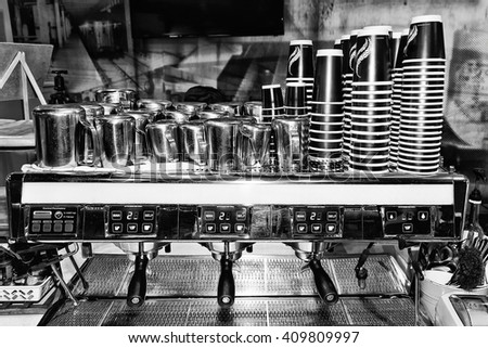 Black white image of industrial large scale barista coffee machine in a cafe ready to serve customers with piles of cups and milk pots around counter. - stock photo