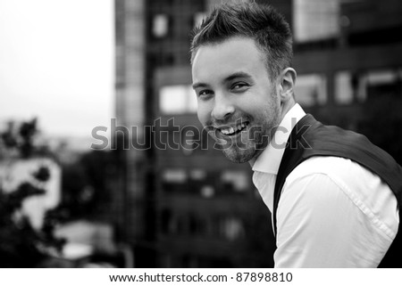 Black-white Portrait of an attractive young man outside. - stock photo
