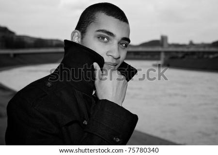 Black-white portrait of stylish young mulatto near town river. - stock photo
