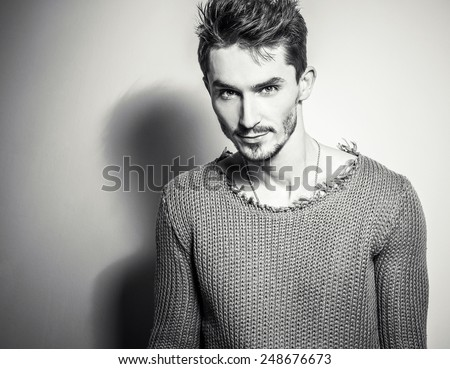 Black-white studio portrait of young handsome man in knitted sweater. Close-up photo. - stock photo
