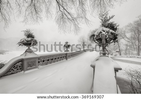 Black & White view of the Bow Bridge in Central Park covered in snow during the blizzard of January 2016. Freezing winter in Manhattan, New York City - stock photo
