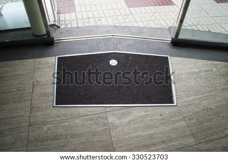 Black with metal frame mat on the gray stone floor near metal glass sliding door - stock photo