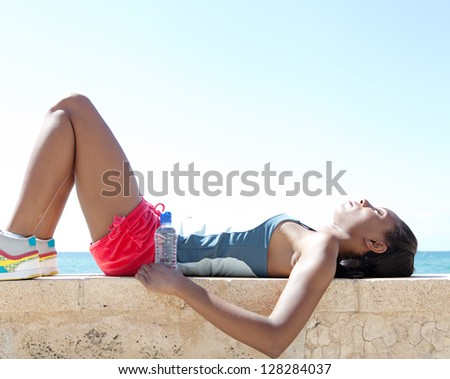 Black woman laying down on a stone wall by the sea, having a break from exercising and sport against a deep blue sky background. - stock photo