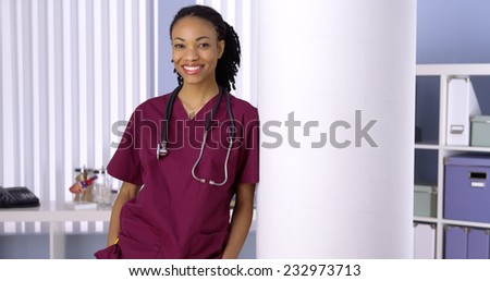 Black woman nurse smiling in office - stock photo