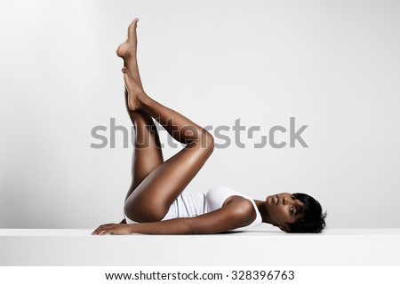 black woman put up her legs and crossed them - stock photo