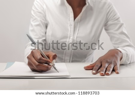 Black woman, with a white shirt, writing - stock photo