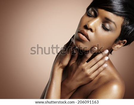 black woman with closed eyes touching her face - stock photo