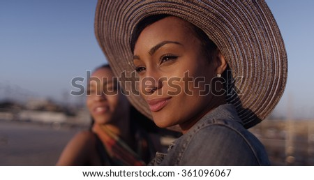 Black women best friends looking out over ocean while standing on pier - stock photo