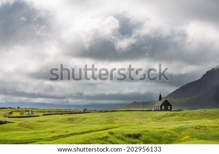 Black wooden church in front of a mountain chain and stormy clouds in Budir, Iceland - stock photo