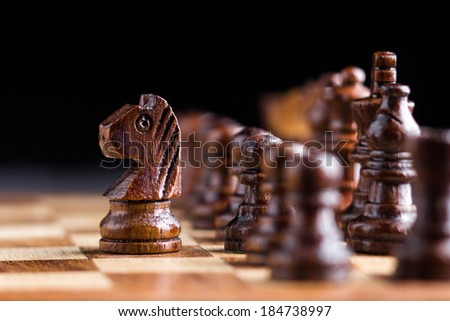 Black wooden horse chess piece in front of chess set. - stock photo