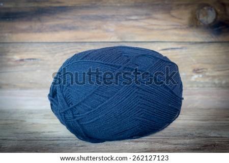 black wool yarn on wood. - stock photo
