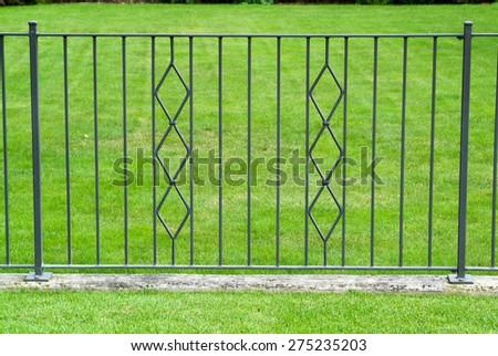 Black wrought iron gate in a beautiful green garden - stock photo