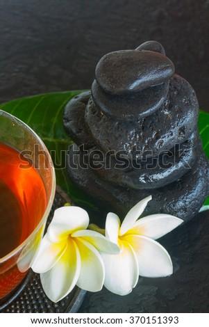 black zen stones with frangipani flowers and green fresh leaf - stock photo