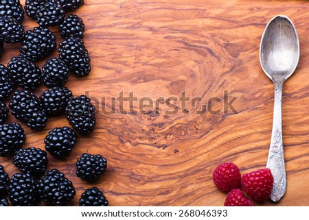 Blackberry on wood with lots copyspace and metal vintage spoon on a side - stock photo