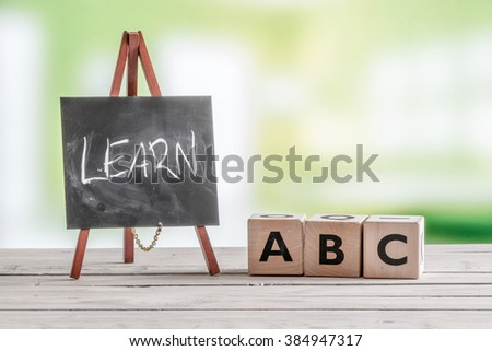 Blackboard and cubes with alphabet sign on a table - stock photo