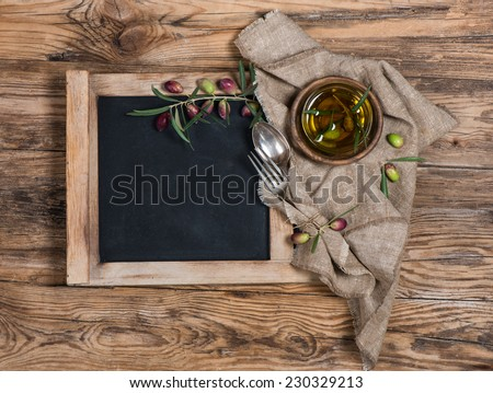 blackboard for menu on wooden table with olives, olive oil , knife and fork  over wooden table  - stock photo