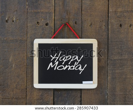 Blackboard hanging on a old wooden wall with phrase Happy Monday. - stock photo