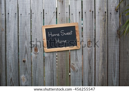 Blackboard Home sweet home sign on wooden fence - stock photo