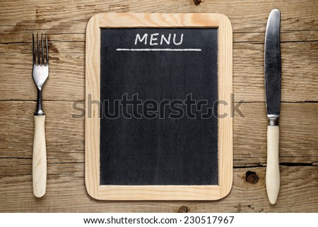 Blackboard menu, fork and knife on old wooden background - stock photo