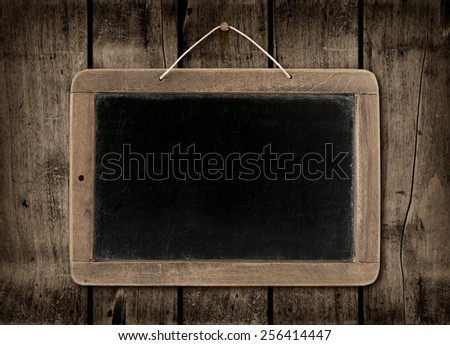 Blackboard on a old dark wood wall background texture - stock photo