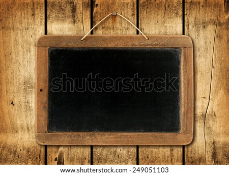 Blackboard on a old wood wall background texture - stock photo