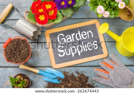 Blackboard on a plant table with garden tools - Garden Supplies - stock photo