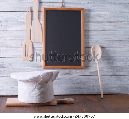 Blackboard on wooden surface and serving spoons - stock photo