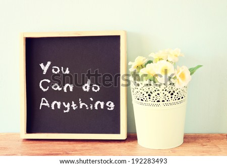 blackboard over shelf with the phrase you can do anything. motivational concept - stock photo