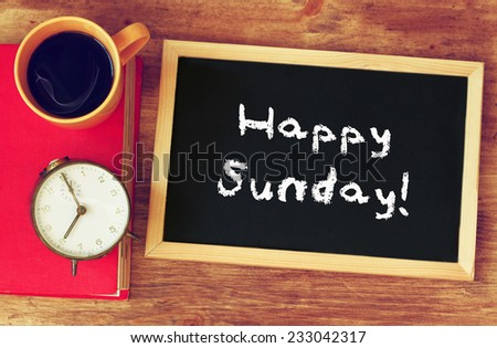 blackboard over wooden table with cup of coffee and  and the phrase it's happy sunday - stock photo