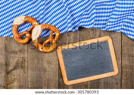 Blackboard with a bavarian diamond pattern and pretzels - stock photo