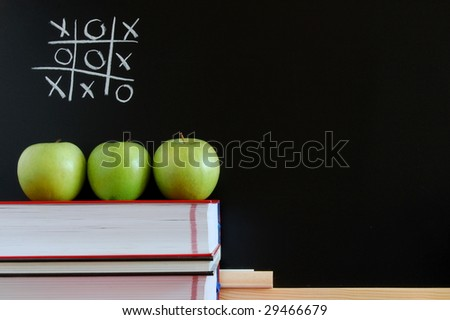 blackboard with apples and books showing a concept for education - stock photo
