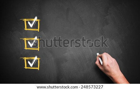 blackboard with 3 checked rows and a hand with chalk, ready for customization with own checklist items - stock photo