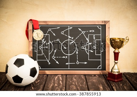 Blackboard with drawn soccer game strategy. Ball, trophy and medal - stock photo