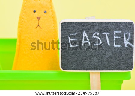 Blackboard with easter bunny on the background on yellow paper background - stock photo