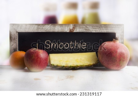 Blackboard with fruit and smoothie bottles - stock photo